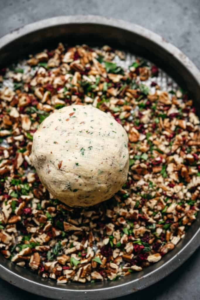 overhead of a vegan cheese ball on a plate of nut coating before it's covered