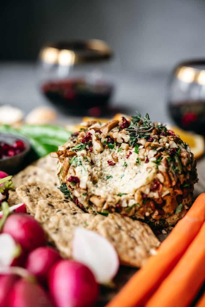 close up side view of vegan cheese ball on platter