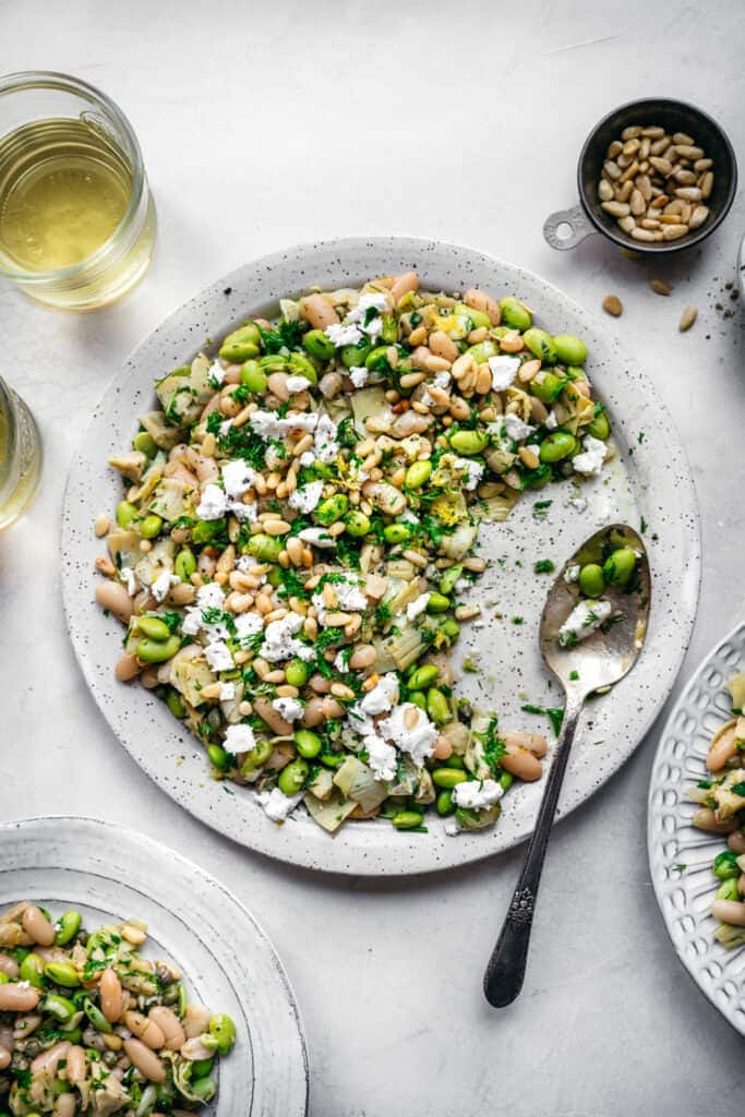 overhead view of white bean salad with edamame, artichokes, pine nuts and feta on a white plate with serving spoon