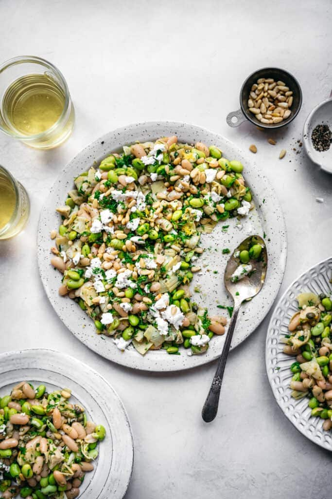 overhead view of white bean salad with edamame, artichokes, pine nuts and feta on a white plate with serving spoon and white wine