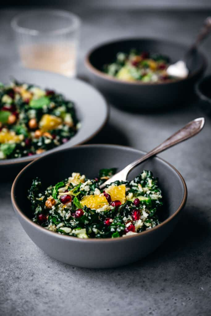 side view of bowl of cauliflower rice and kale salad with oranges and pomegranate