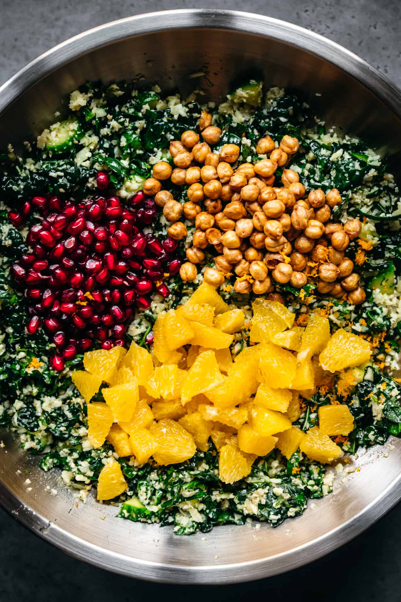 overhead view of cauliflower kale salad in mixing bowl with oranges, pomegranate and chickpeas