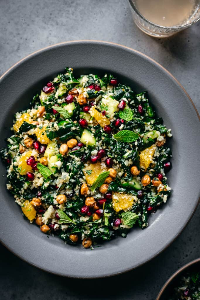 overhead view of mediterranean cauliflower rice salad with kale in a beautiful grey bowl