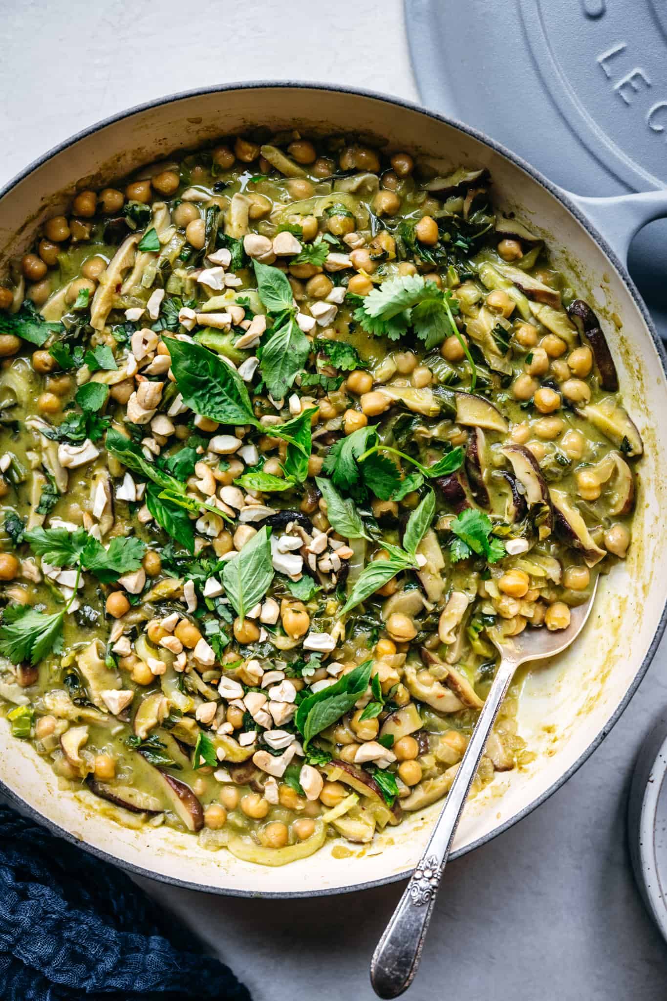 close up overhead view of vegan thai green curry with chickpeas in braiser