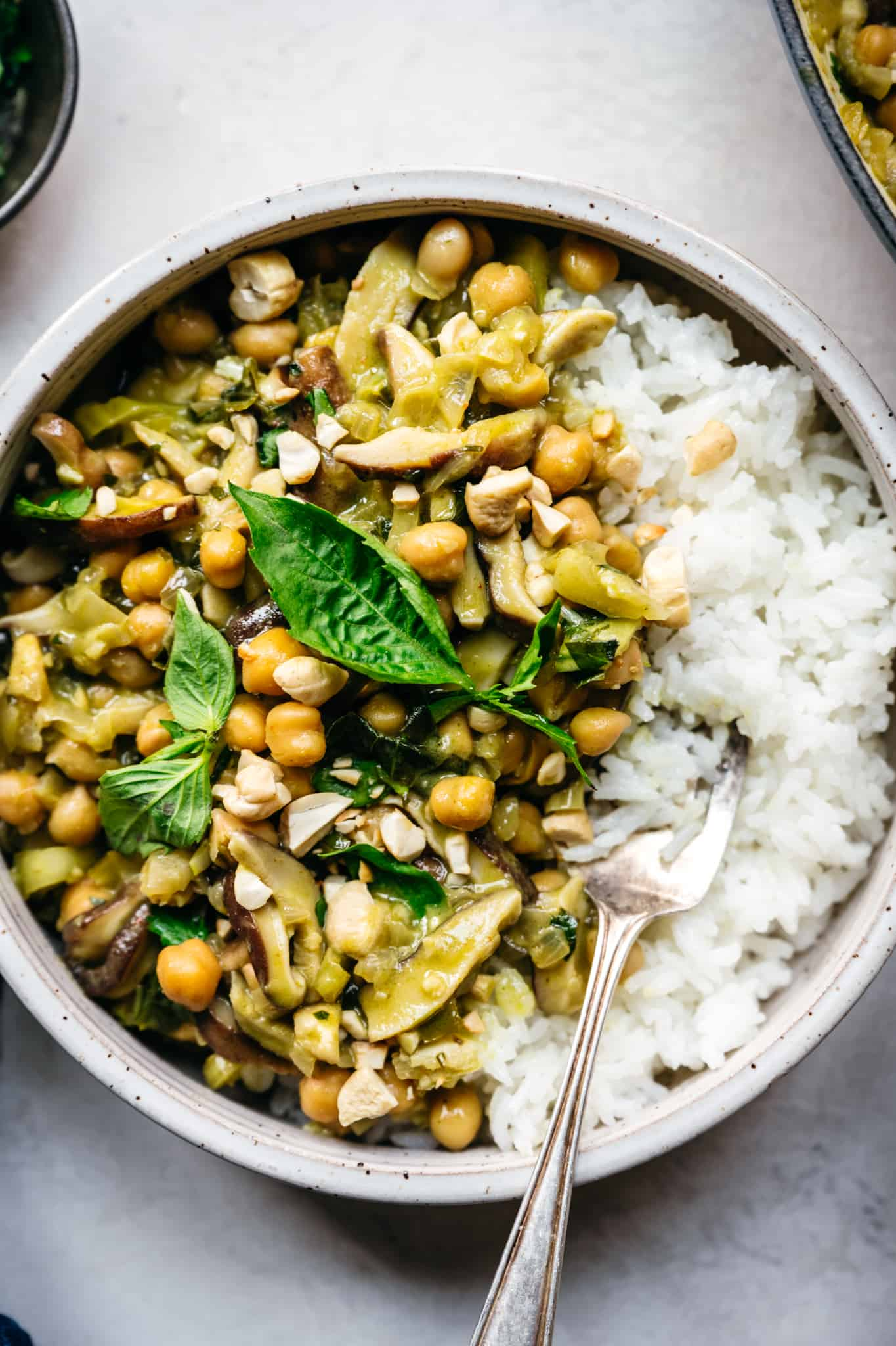 vegan green curry with chickpeas and mushrooms served over white rice in bowl