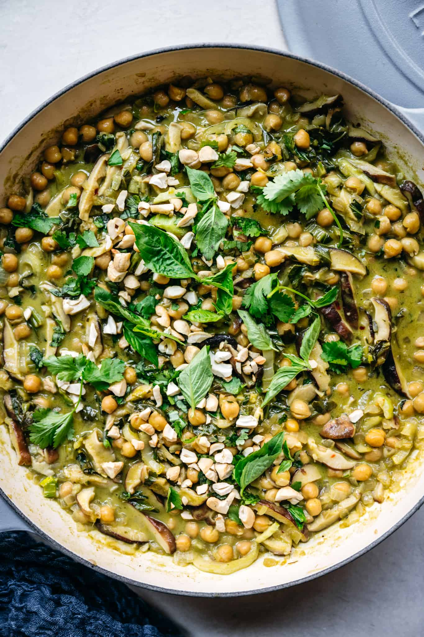 close up overhead of vegan chickpea green curry with Thai basil and cilantro garnish
