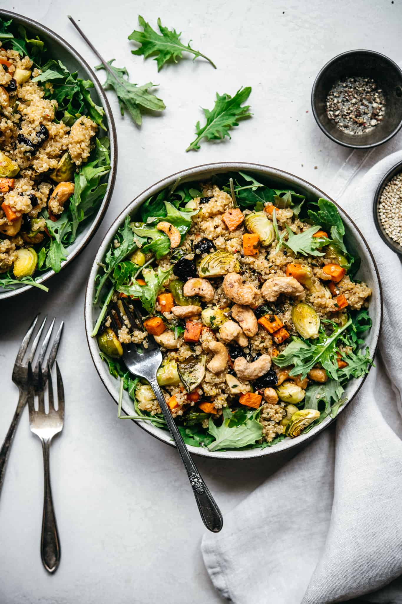 overhead view of two bowls of quinoa salad with roasted vegetables on white background