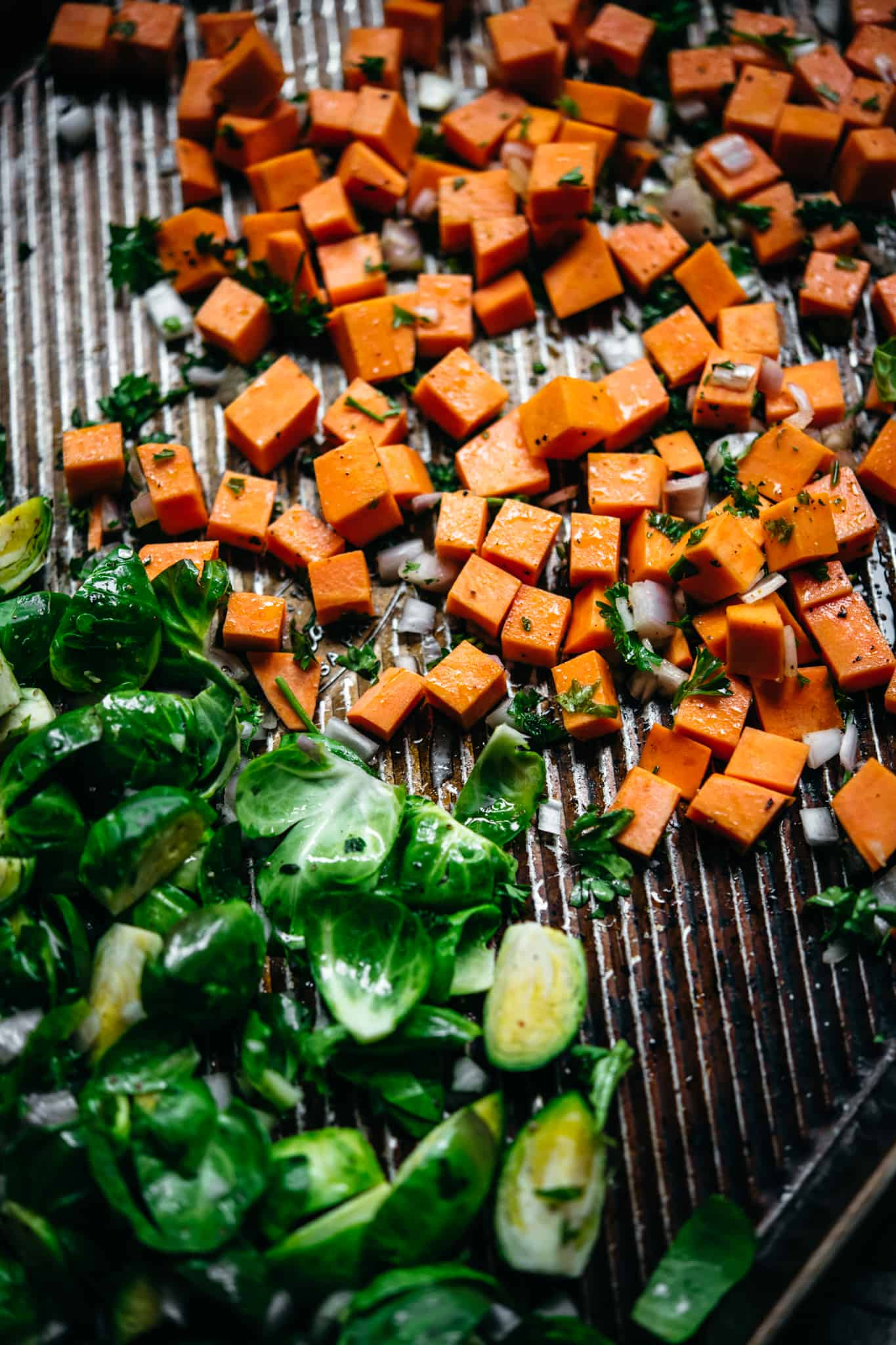 close up view of diced sweet potato and brussels sprouts on a sheet pan before roasting