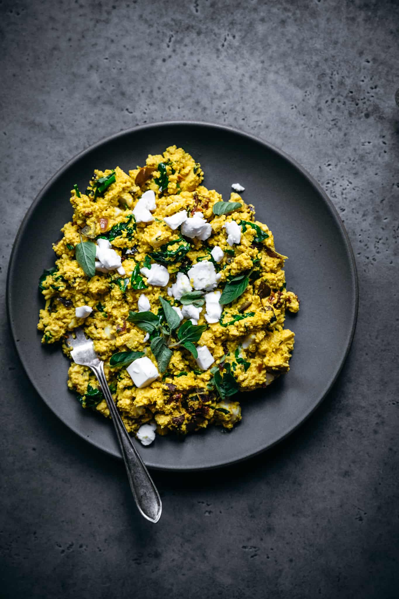 overhead view of greek scrambled tofu on grey plate with fork