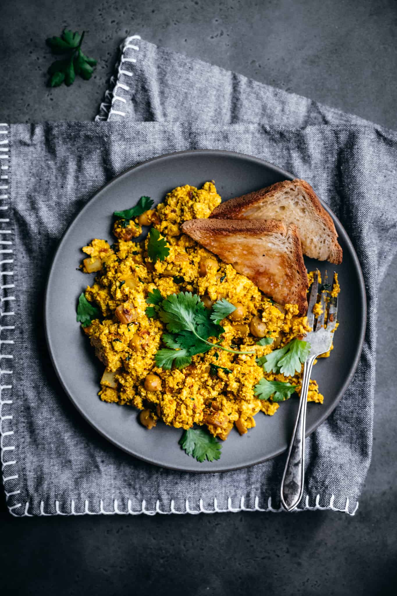 overhead view of curry-spiced vegan scrambled tofu on a grey plate with toast and fresh cilantro