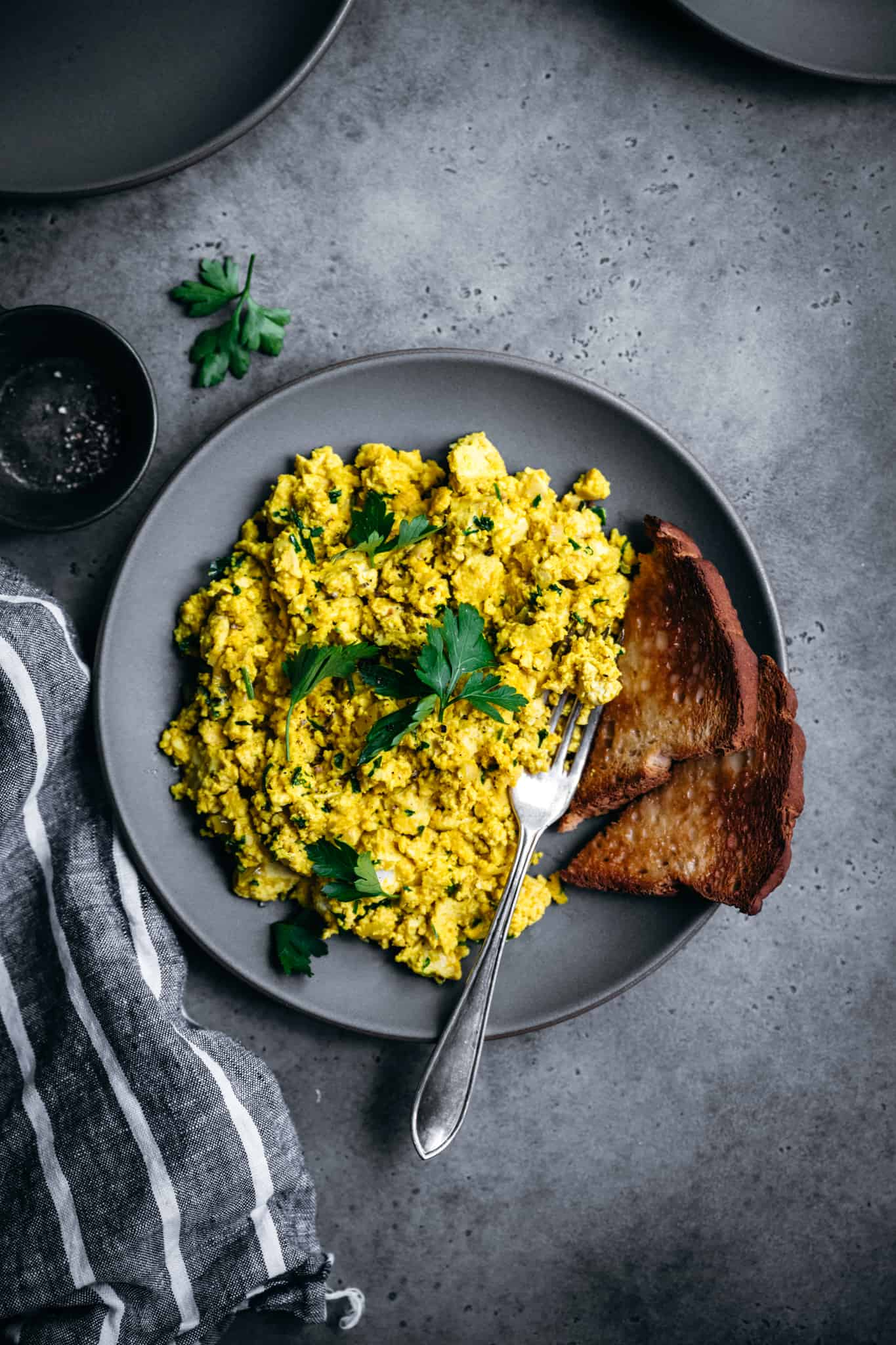overhead view of cheesy herbed vegan tofu scrambled eggs on a plate with toast
