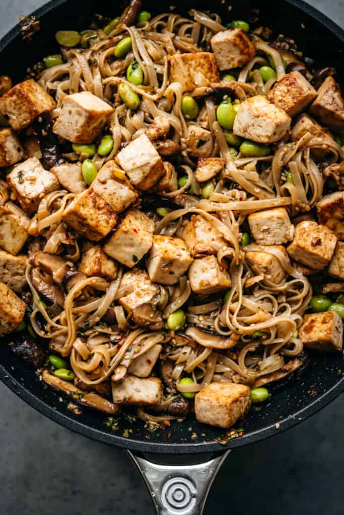 close up view of vegan rice noodles with crispy tofu in a skillet