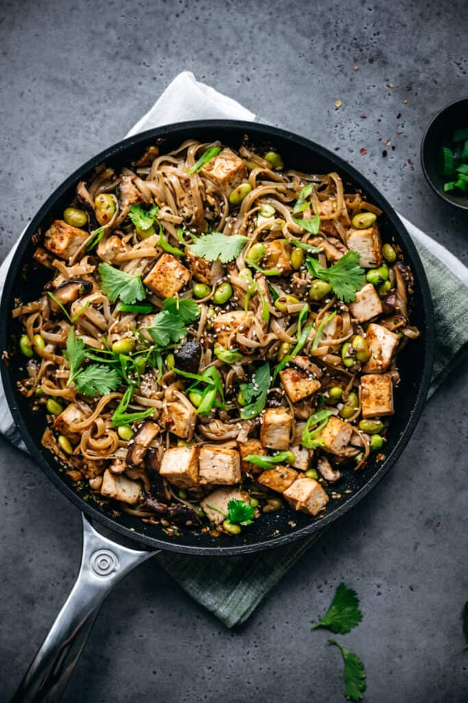 vegan rice noodles with tofu, edamame and scallions in a nonstick pan