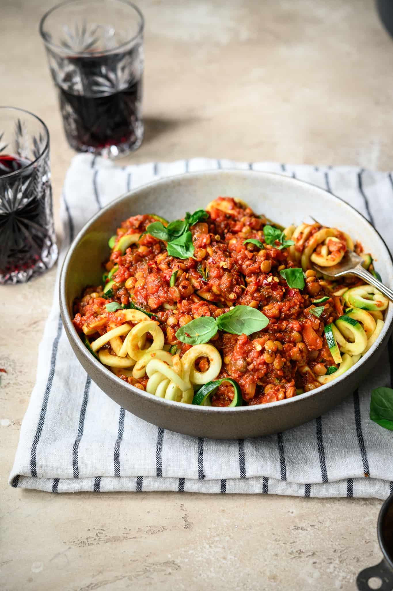 side view of vegan lentil bolognese sauce over zucchini noodles