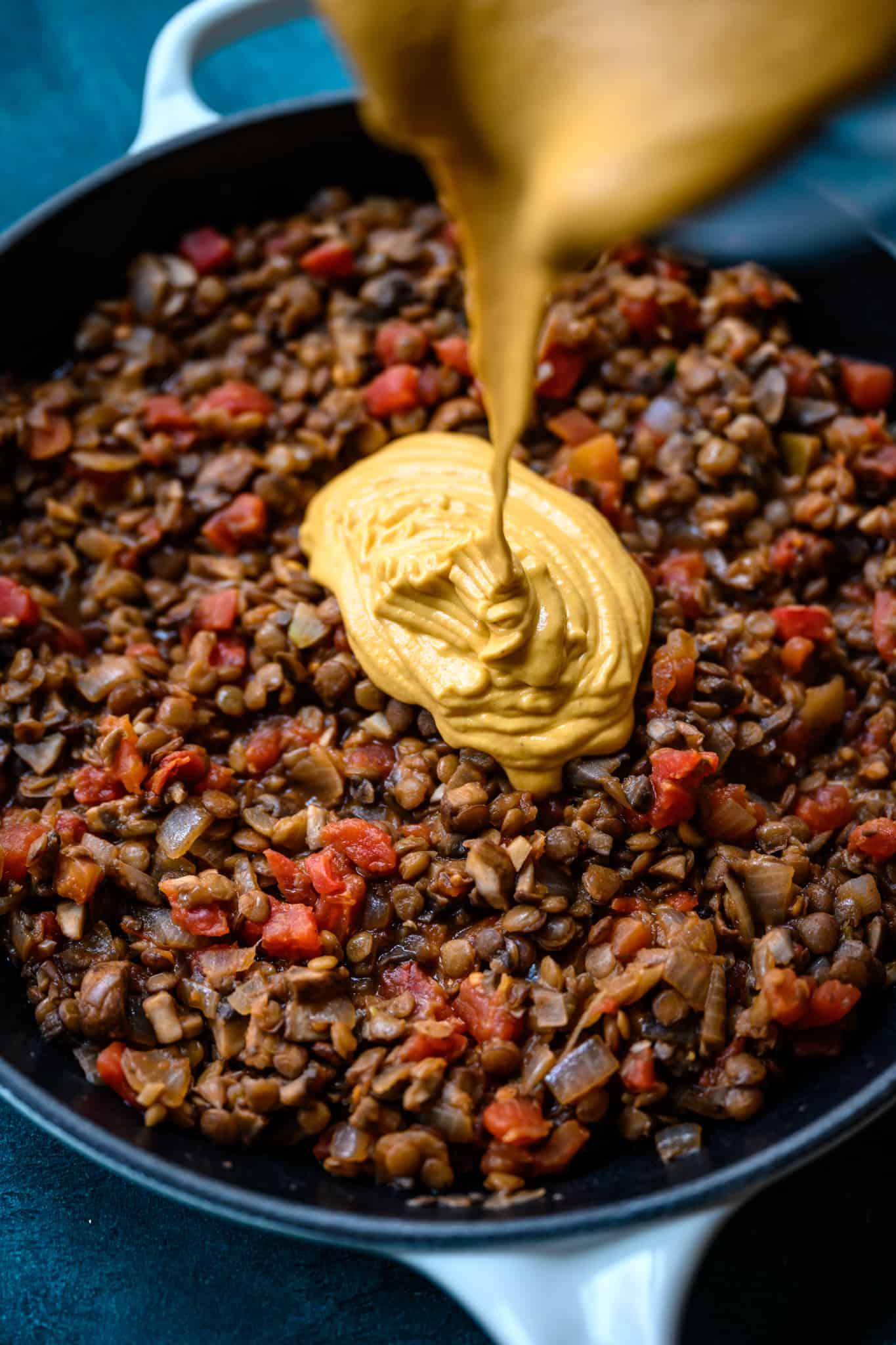 pouring vegan queso dip into vegan lentil mushroom mixture