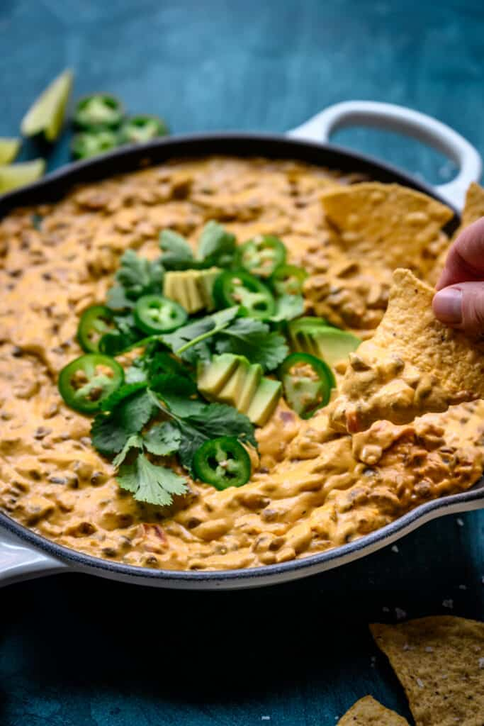 side view of person dipping tortilla chip into vegan chile con queso dip
