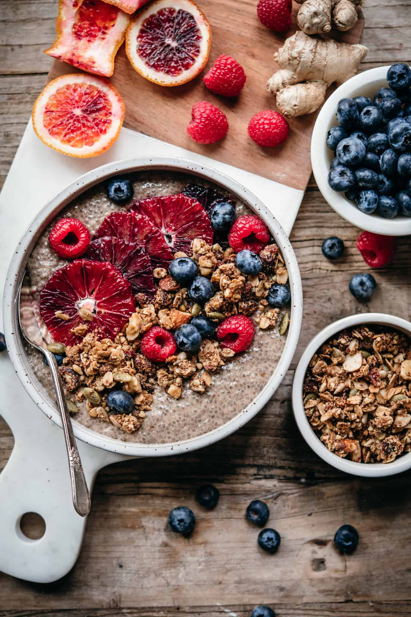 overhead view of chai chia pudding in white ceramic bowl with berries and granola