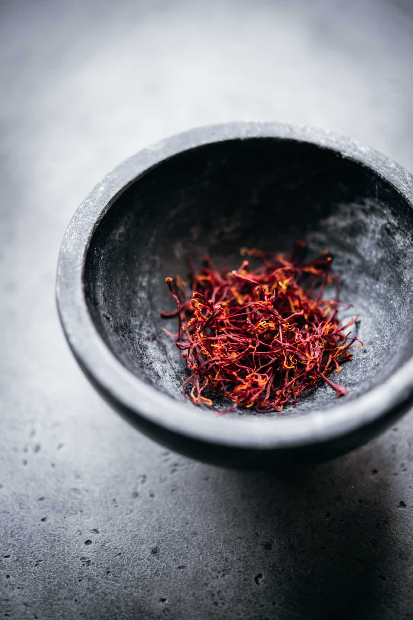 Close up view of saffron threads in a small black bowl