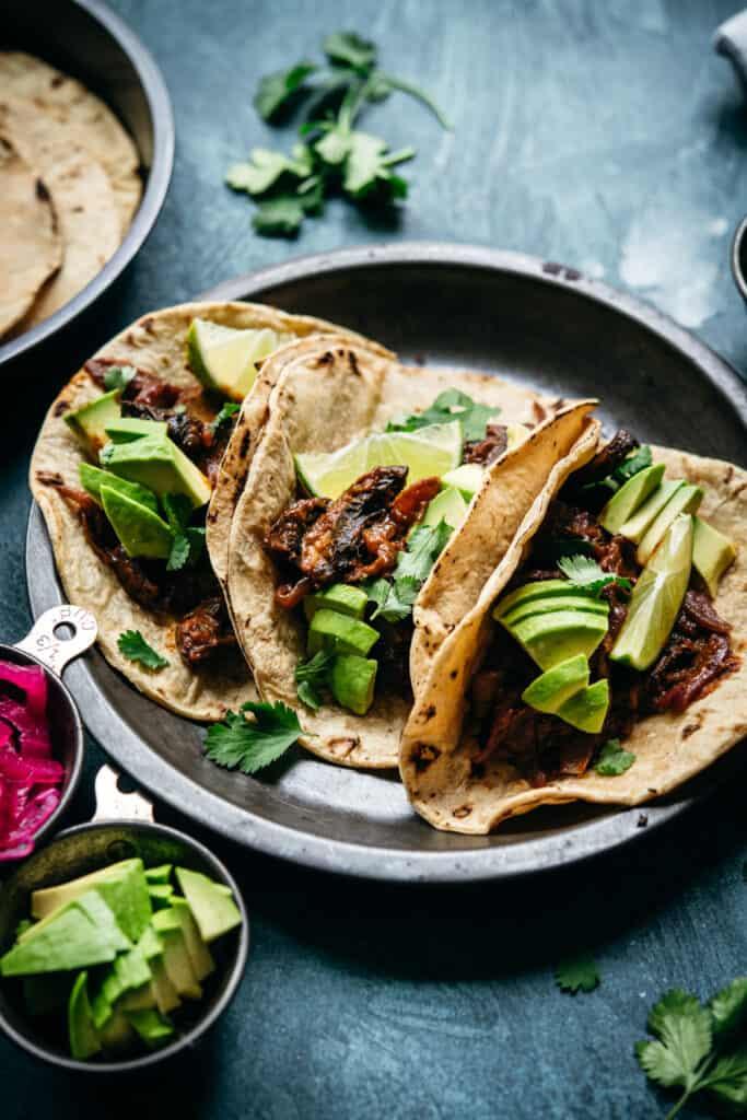 side view of vegan mushroom al pastor tacos in charred tortillas with avocado
