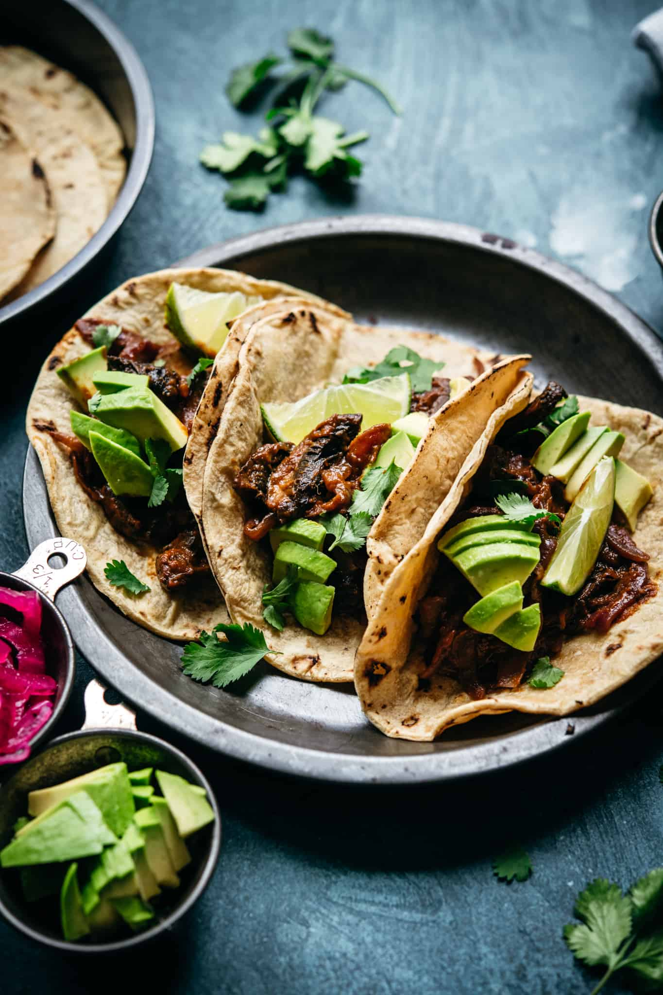 side view of vegan mushroom al pastor tacos in charred tortillas with avocado