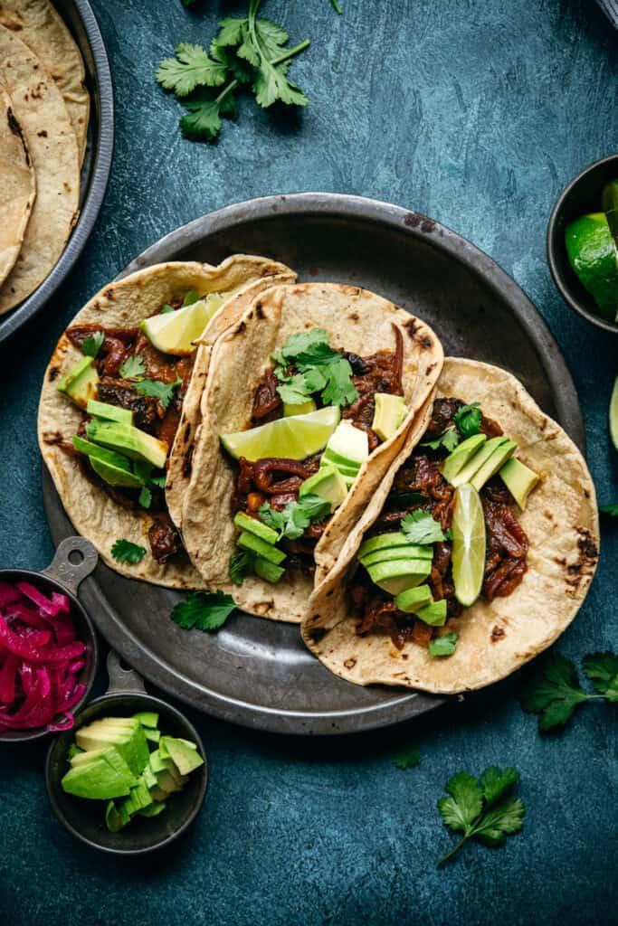 overhead view of vegan mushroom al pastor tacos with avocado and lime