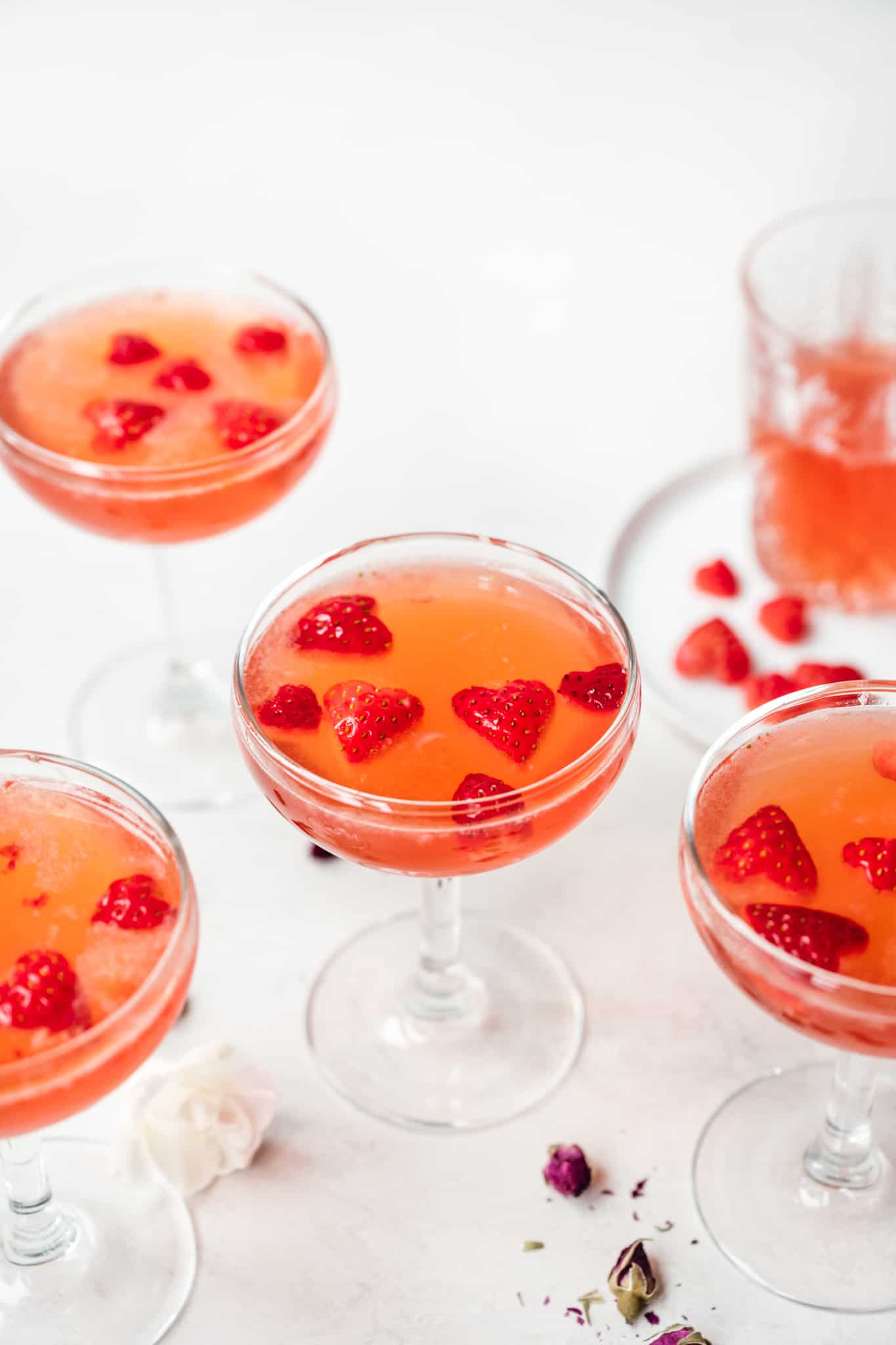 side view of valentine's day cocktails garnished with strawberry hearts