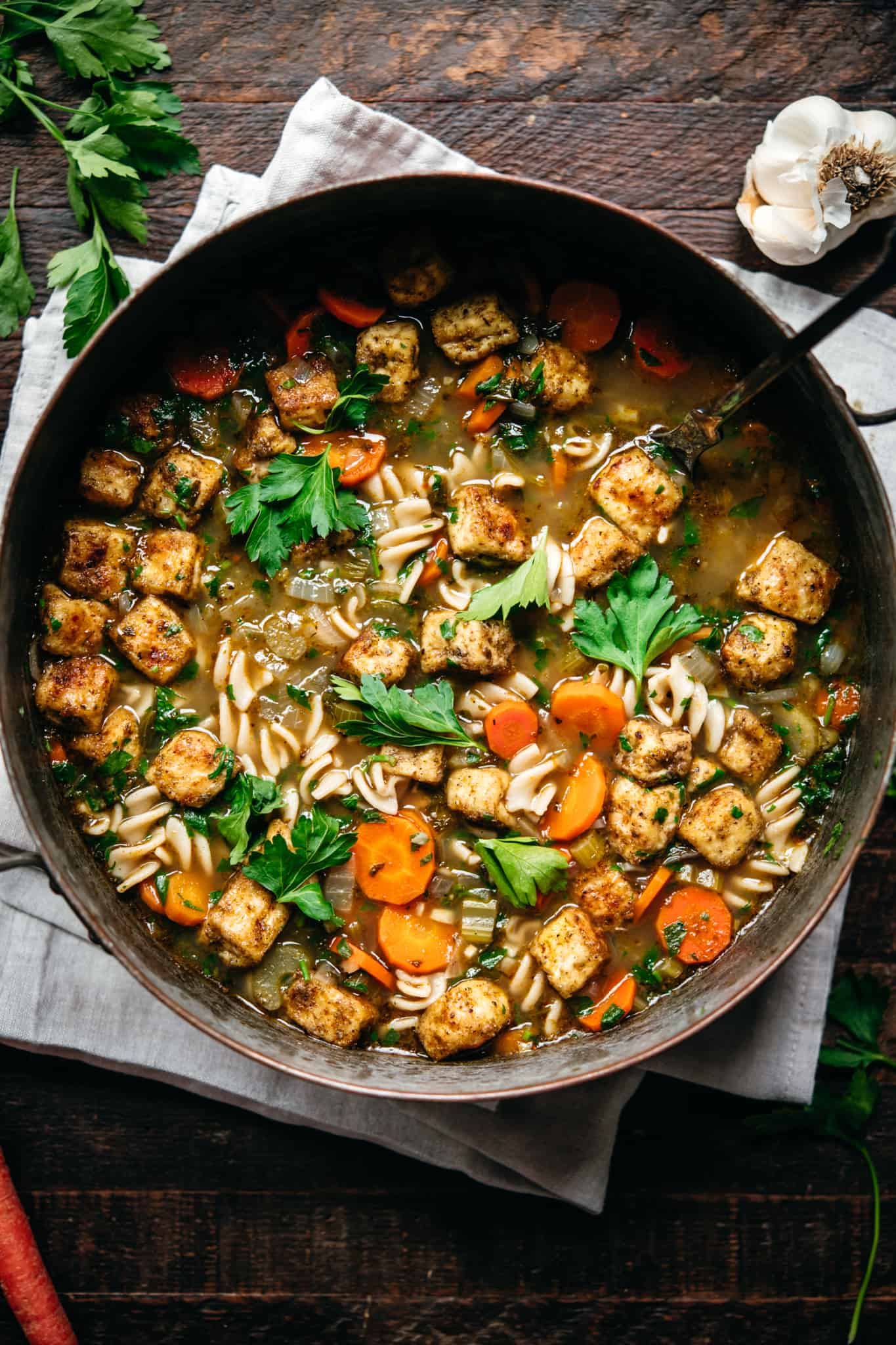 overhead view of vegan chicken noodle soup with crispy tofu in large copper pot