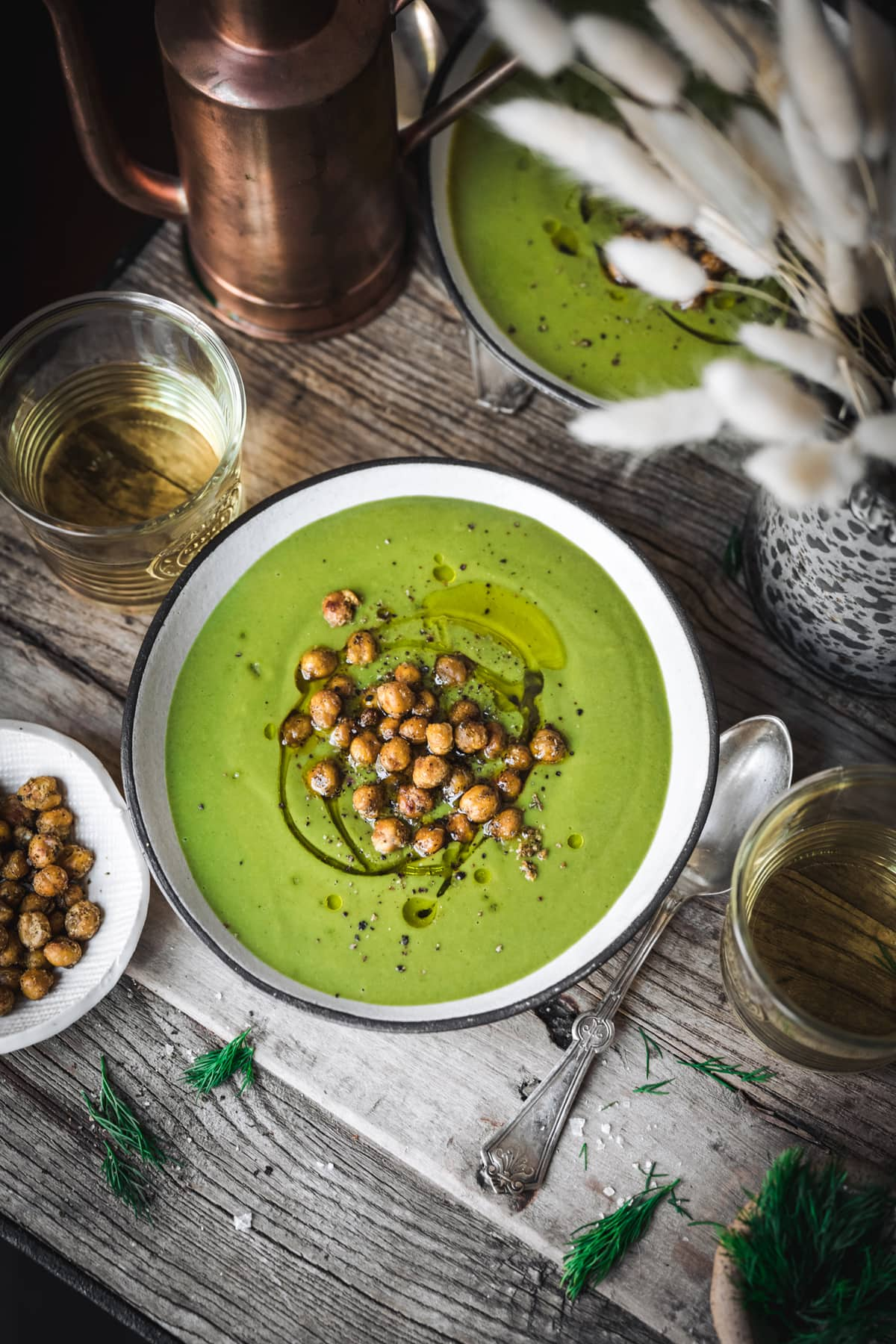 overhead view of creamy vegan broccoli spinach soup on wood table with crispy chickpeas