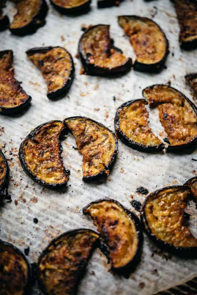 close up view of miso glazed oven roasted eggplant slices on sheet pan