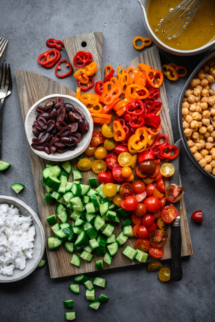 overhead view of greek chickpea salad ingredients on cutting board