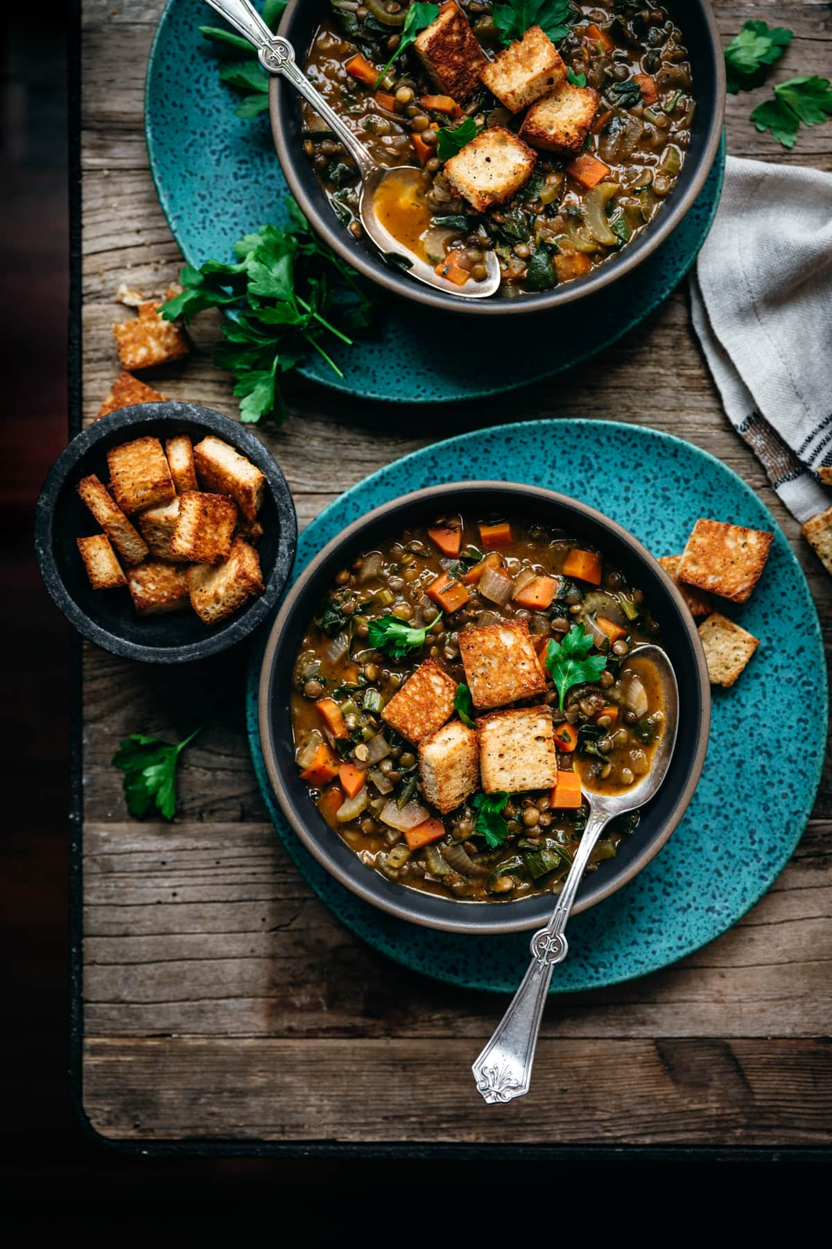 overhead view of vegan lentil stew with garlic croutons on wood table