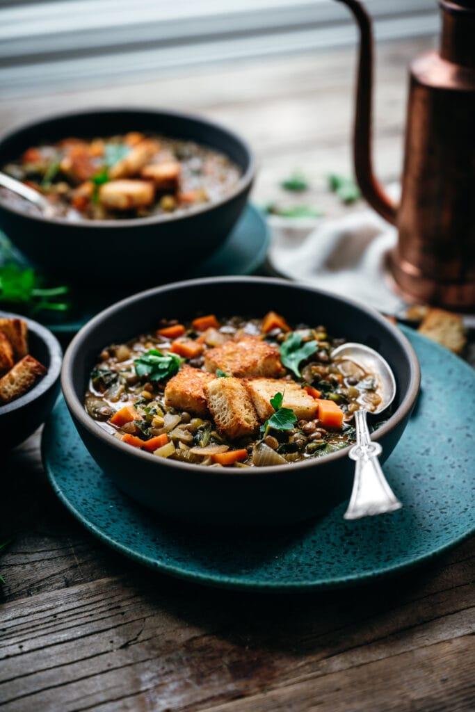 backlit side view of vegan lentil vegetable stew in blue bowl on wood table