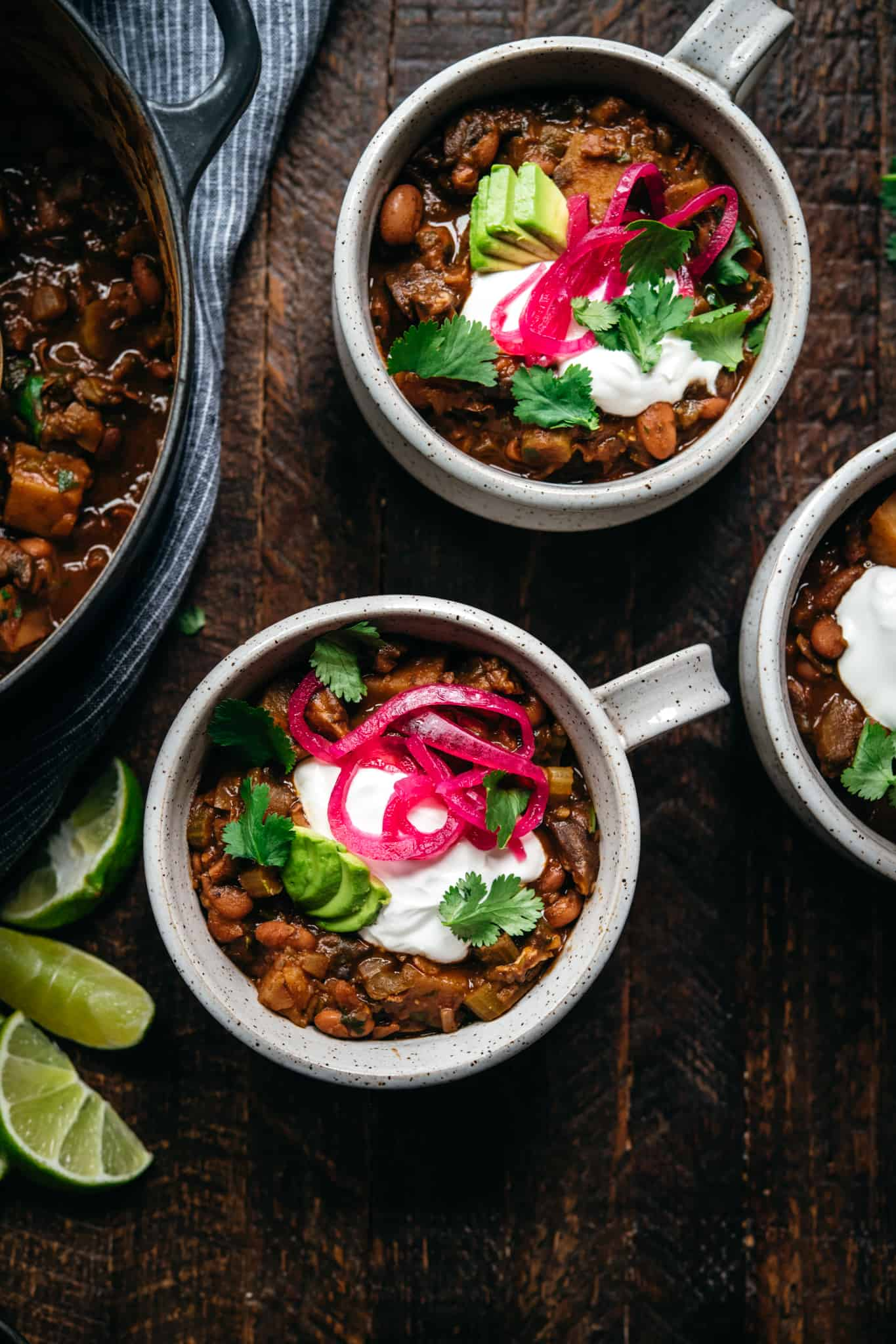 overhead view of vegan pinto bean chili in white ceramic bowls on wood background