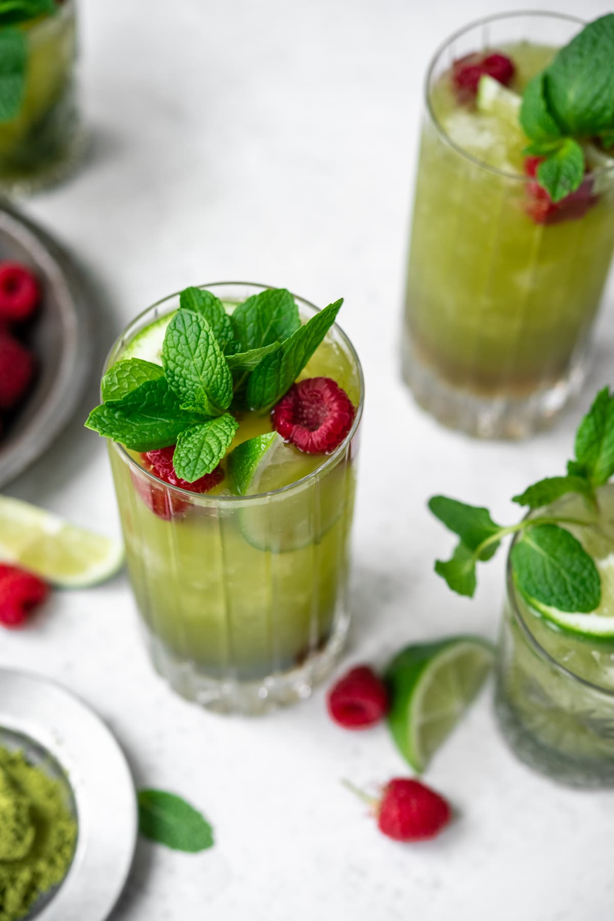 close up side view of matcha mojito with bunch of fresh mint