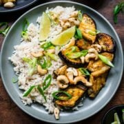 Overhead view of miso eggplant with lime wedges, rice, and cashews.