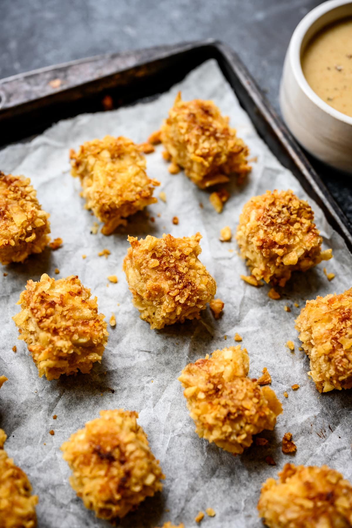 close up side view of baked tofu nuggets on sheet pan after baking