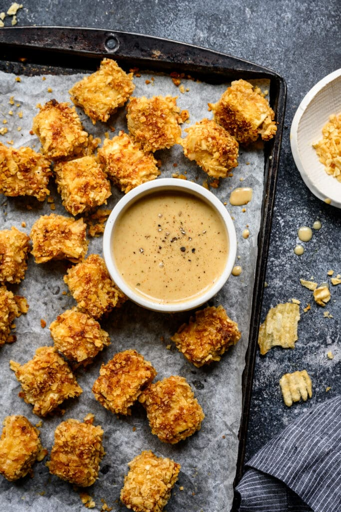 overhead view of crispy baked tofu nuggets on sheet pan with bowl of honey mustard