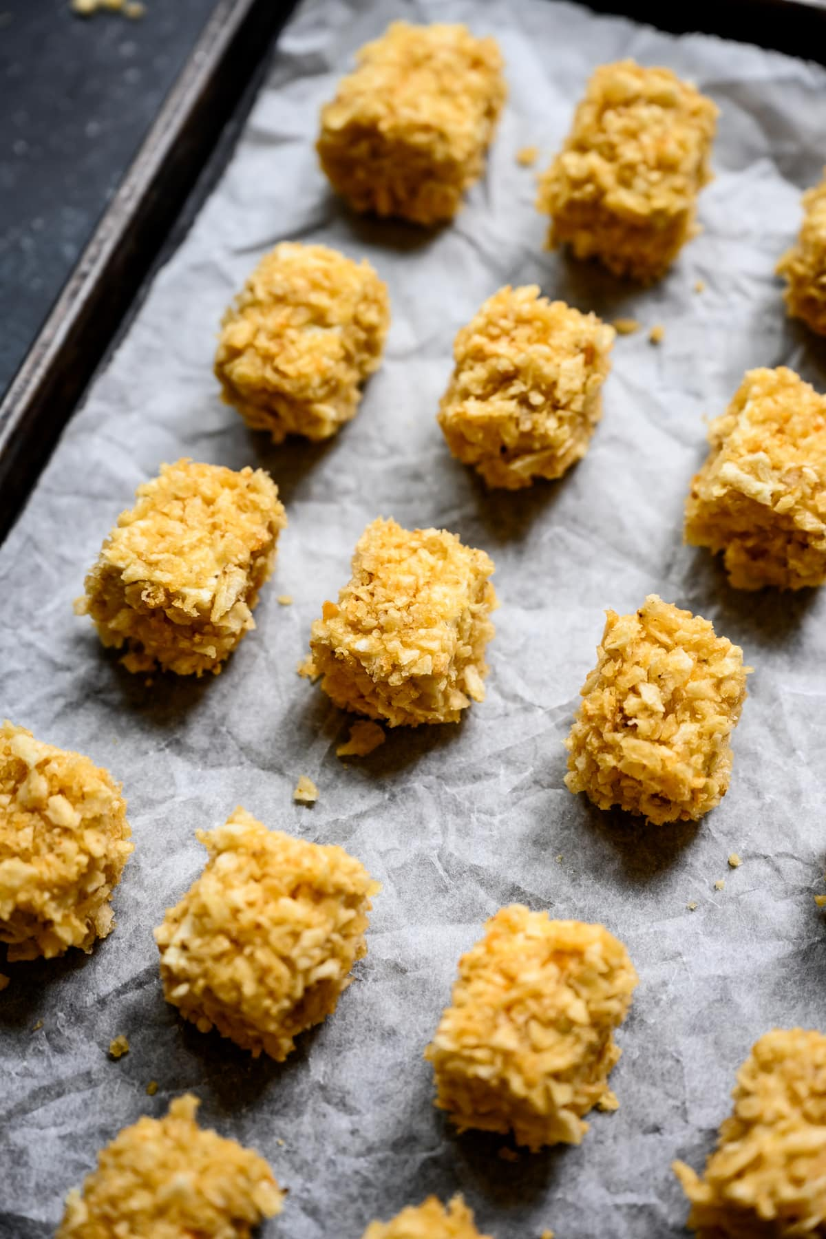 close up side view of baked tofu nuggets on sheet pan before baking