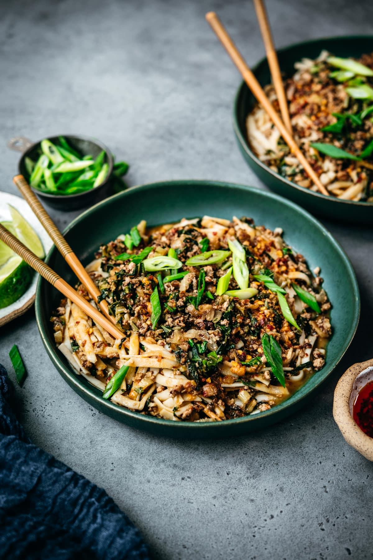 side view of vegan dan dan noodles in blue bowl with chopsticks