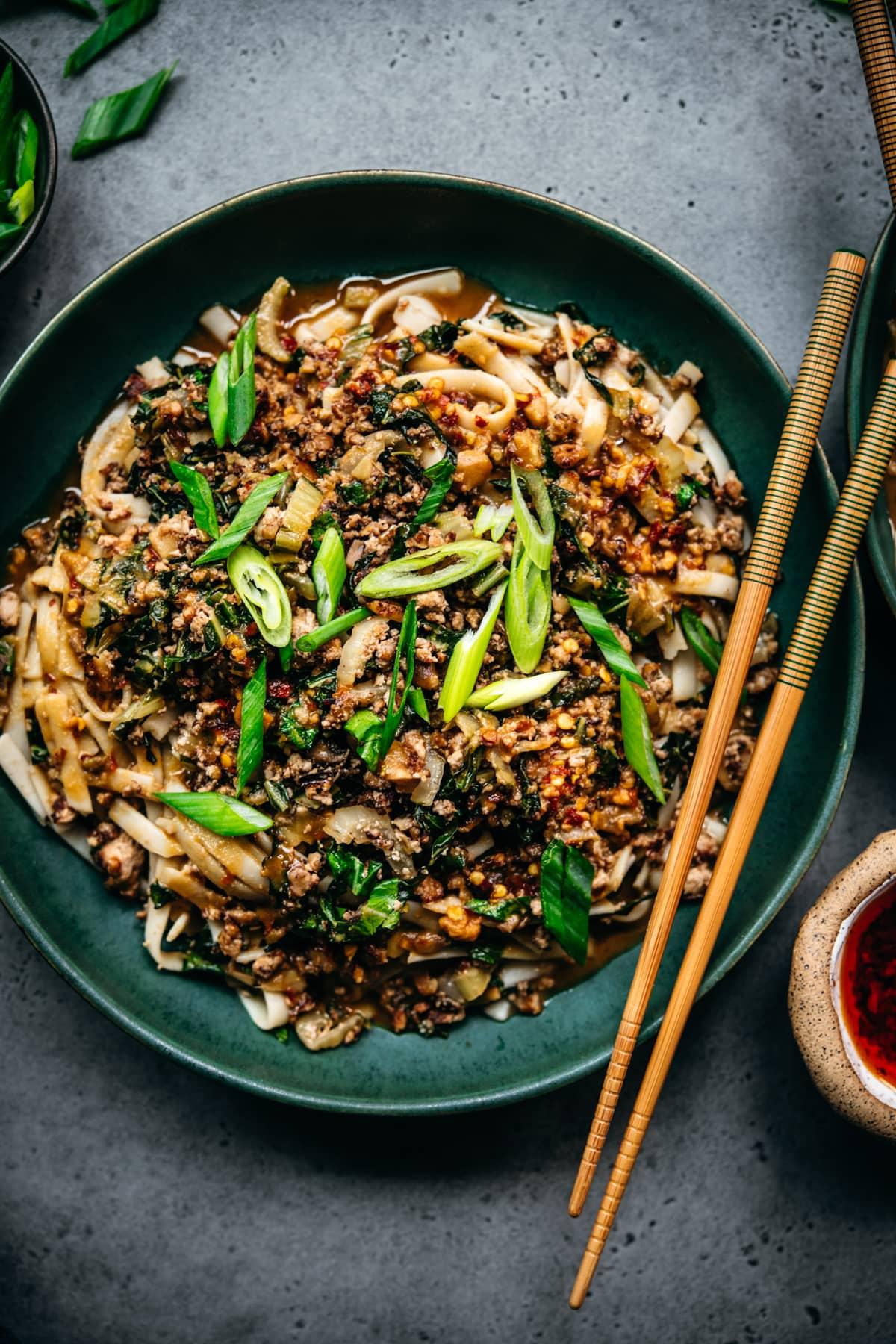 overhead view of vegan dan dan noodles in bowl with chopsticks
