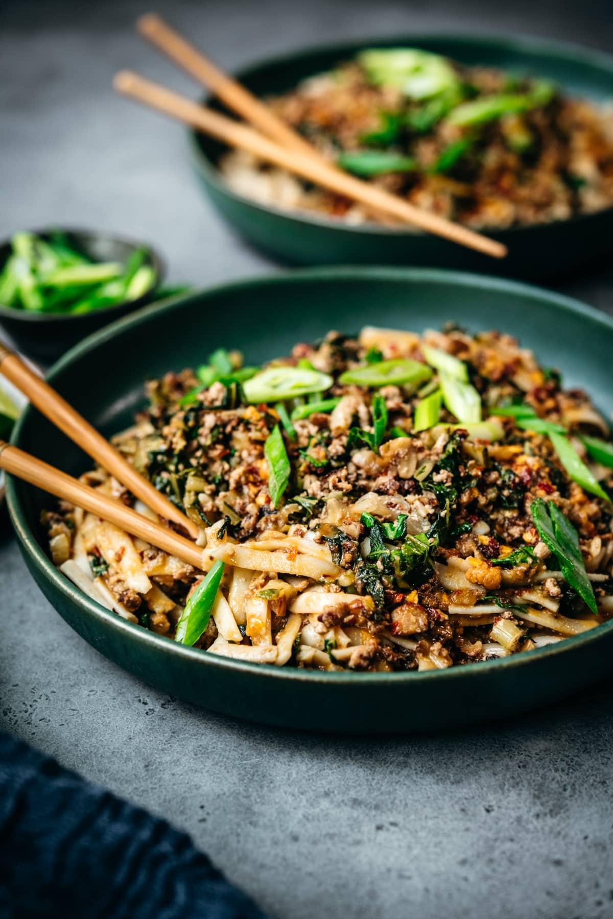side view of vegan dan dan noodles in blue bowl