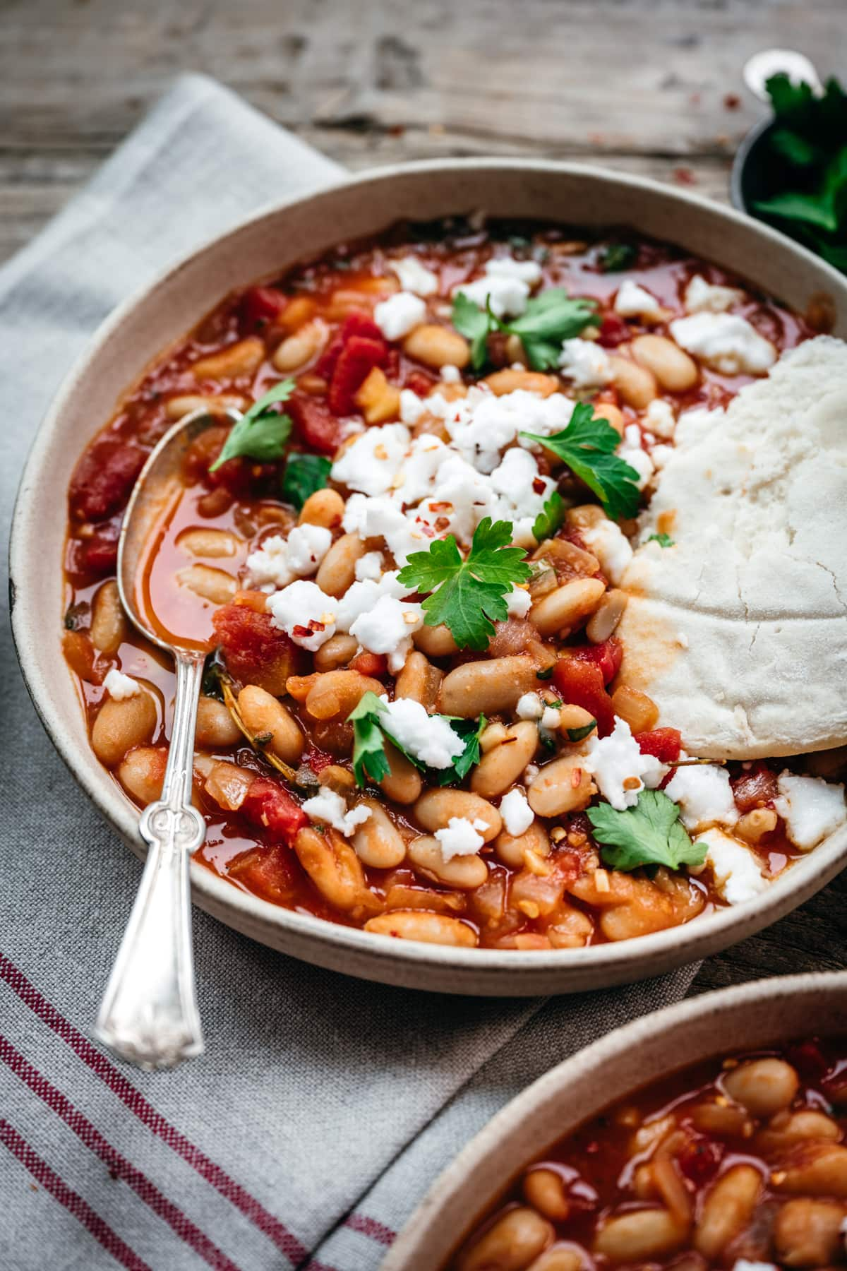 close up side view of tomato white bean stew in a bowl with feta and pita bread