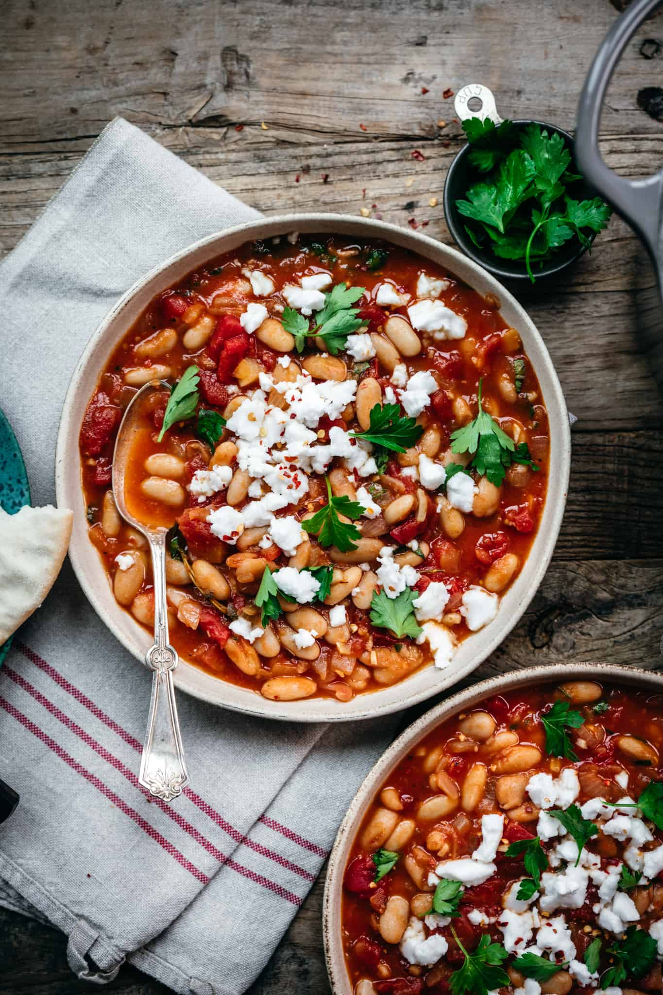 overhead view of vegan tomato white bean stew with feta and parsley in white bowl with spoon