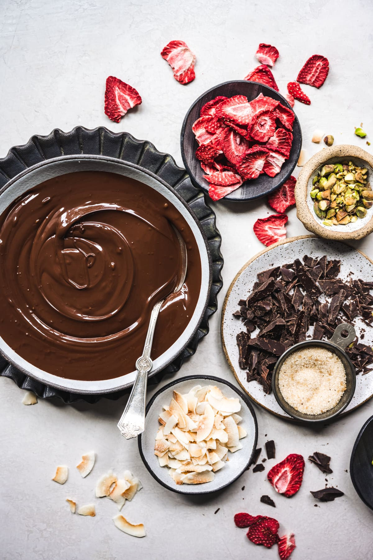 overhead view of ingredients for dark chocolate bark with strawberries, coconut and pistachios