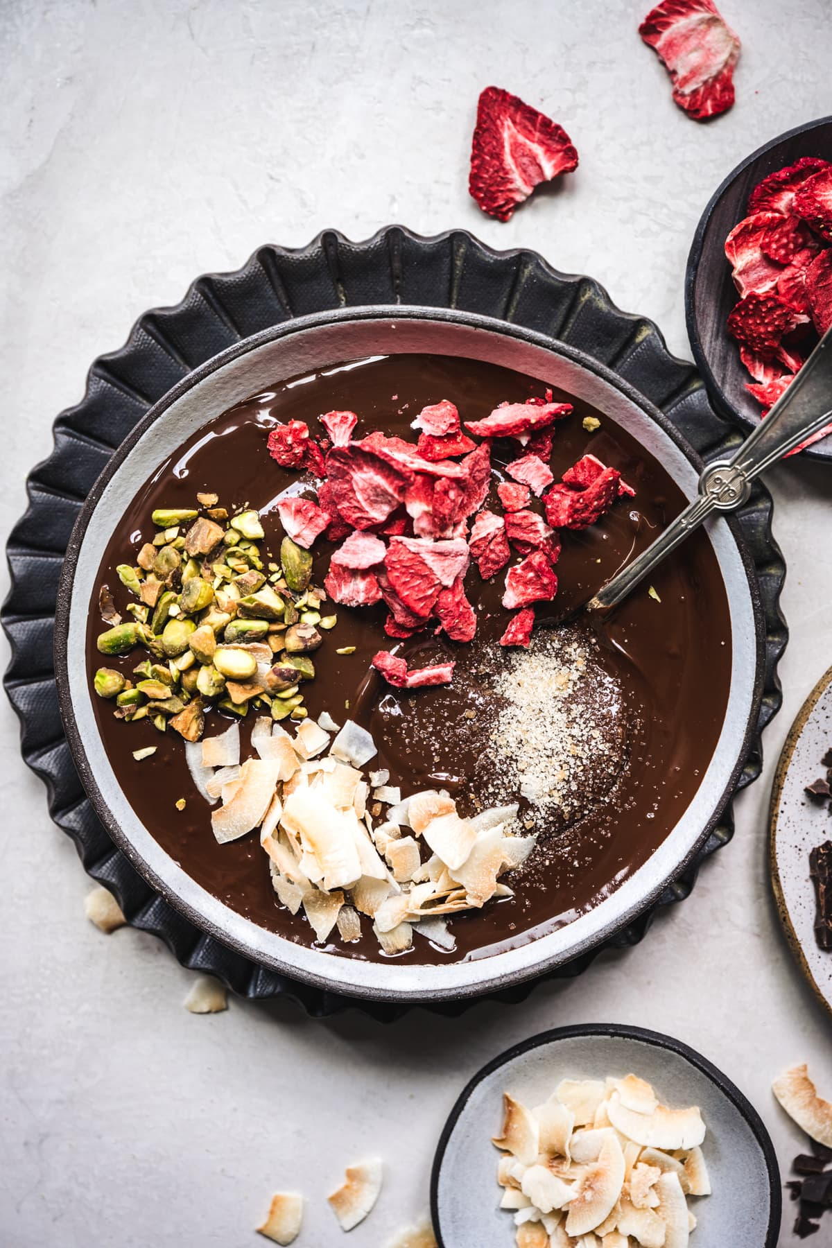 overhead view of melted dark chocolate with strawberries, pistachios and coconut