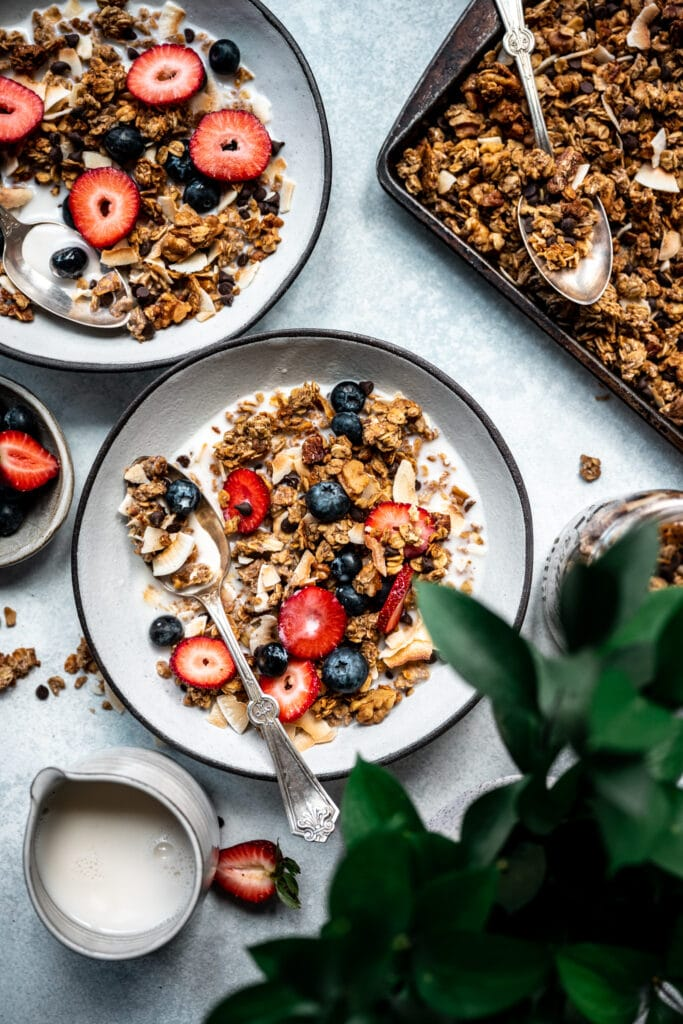 overhead view of banana bread granola in bowl with milk and berries