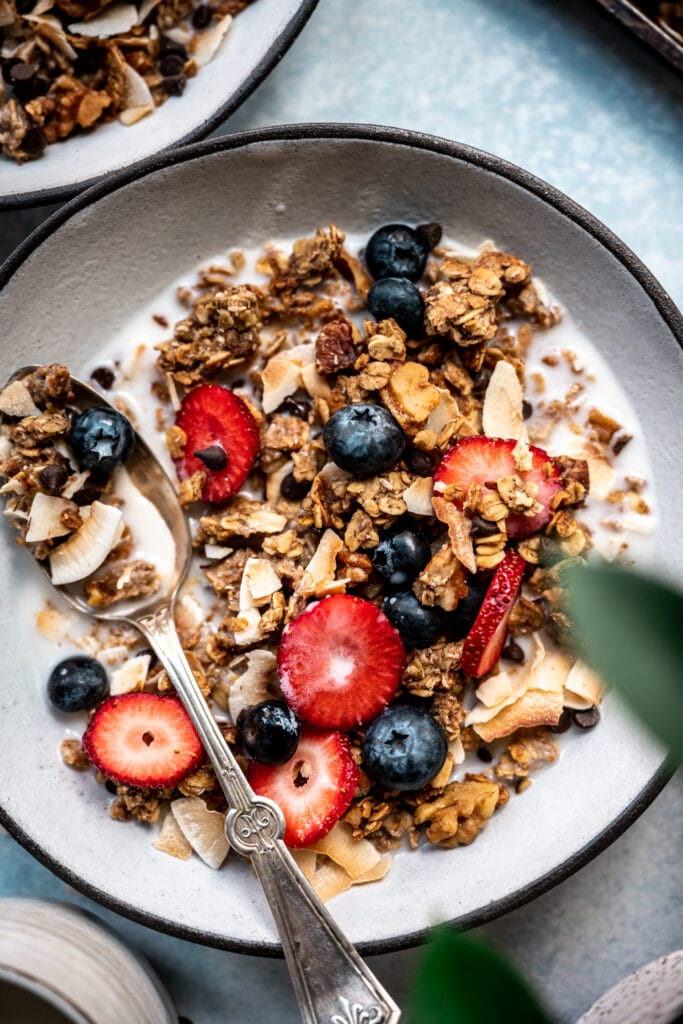 close up overhead view of banana bread granola in bowl with milk, sliced strawberries and blueberries