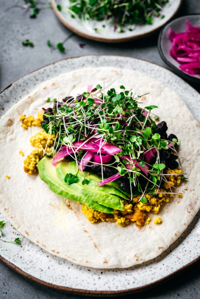 side view of open-faced vegan breakfast burrito with scrambled tofu