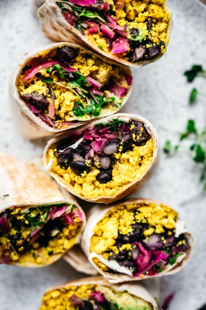 close up view of vegan scrambled tofu breakfast burritos with black beans and avocado