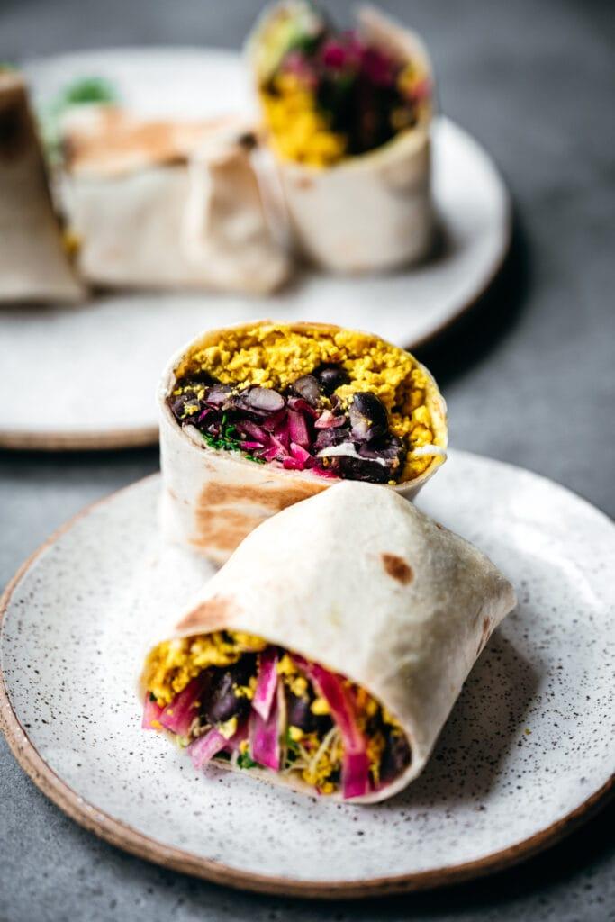 side view of vegan breakfast burritos cut in half on a plate
